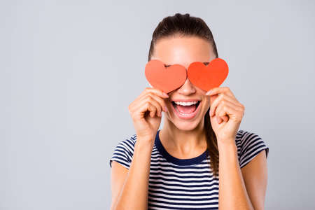 Photo pour Close up photo beautiful amazing she her lady ideal teeth kind hide eyes two red paper hearts shape figure postcards guess who game boyfriend wear blue white striped t-shirt isolated grey background - image libre de droit