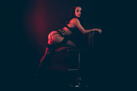Foto de Profile side view portrait of lovely adorable attractive perfect sporty shape form wavy-haired lady wearing swordbelt leaning on office chair enjoying isolated over red light black background - Imagen libre de derechos