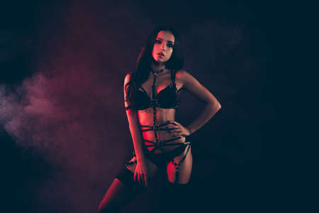Portrait of nice cool gorgeous adorable attractive sportive perfect thin fit form shape line wavy-haired lady wearing swordbelt teasing enjoying life isolated on black red light background