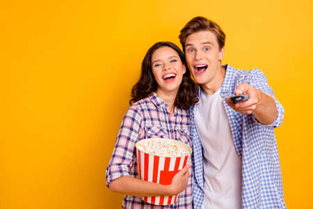 Photo pour Close up photo of pair delighted from gladness he him his she her lady guy choosing channel for watching movie wearing casual plaid shirts outfit isolated on yellow background - image libre de droit
