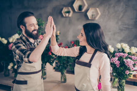 Photo for Close up side profile photo partners she her lady him his he guy clapping arms amazed excited earn big order money compositions bunches fresh flowers owners wear aprons small flower shop room indoors - Royalty Free Image