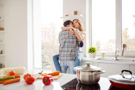 Foto de Close up photo pair beautiful he him his macho she her lady just married desire in love overjoyed hold each other hands bonding hugging touch lips kiss apartments flat bright kitchen room indoors - Imagen libre de derechos
