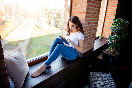 Foto de Nice-looking attractive lovely charming fit slim thin concentrated focused wavy-haired girl sitting on window sill reading ebook news at industrial loft wooden brick style interior indoors - Imagen libre de derechos