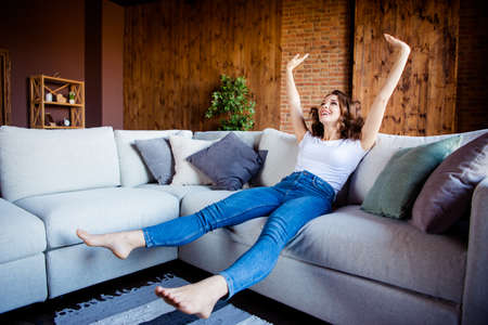 Foto de Full length body size view of her she nice attractive lovely charming cheerful cheery wavy-haired girl sitting on comfortable divan having fun time at industrial loft wooden brick style interior - Imagen libre de derechos