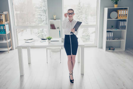 Full length body size photo beautiful she her business lady hands arms hold clipboard documents papers ready conference stand lean table high-heels specs formal-wear white shirt skirt bright office