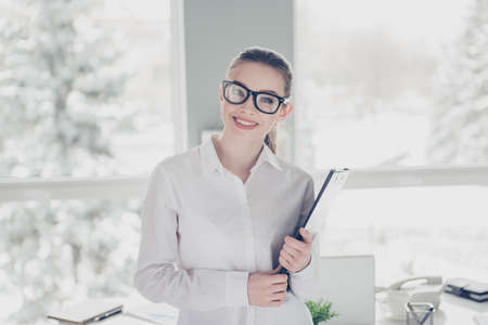 Close up photo beautiful she her business lady eyewear eyeglasses hands arms hold clipboard documents papers ready conference stand table wear specs formal-wear white shirt modern bright office
