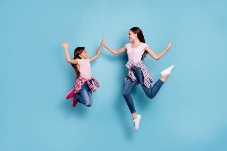 Full length body size view portrait of two nice charming attractive cheerful cheery straight-haired girls having fun clapping palms isolated over bright vivid shine blue turquoise background