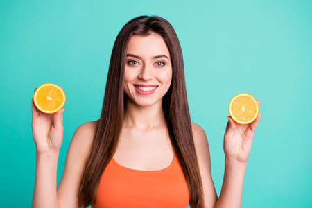 Close up photo beautiful amazing her she lady hold arms two citrus useful slices products advertising nutrition freshness wear casual orange tank-top isolated bright teal turquoise background