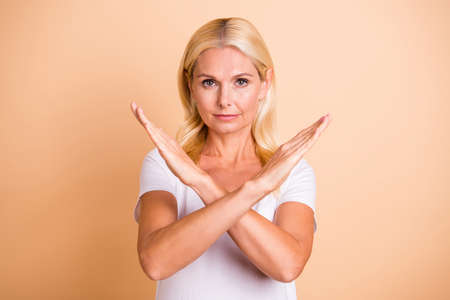 Foto de Photo of lady arms crossed no you will not pass through symbol wear white casual t-shirt isolated pastel beige background - Imagen libre de derechos