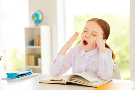 Photo for Close up photo of sad upset kid sit lecture back school tiredness class room close yes dressed white shirt blouse foxy ginger hairstyle haircut disappointed task - Royalty Free Image