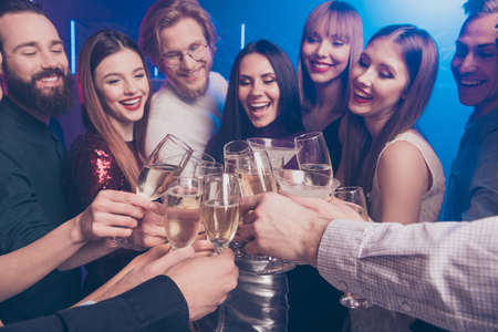Photo for Cropped close-up portrait of nice chic winsome adorable glamorous luxury attractive fashionable gorgeous cheerful glad ladies and guys having fun clinking wineglasses sparkles at fogged lights nightclub - Royalty Free Image