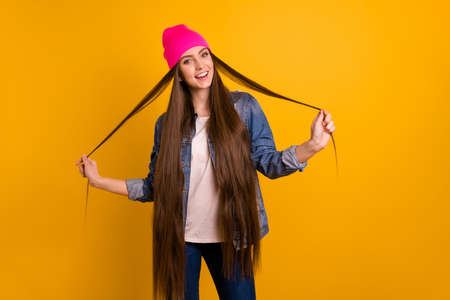 Foto de Close up photo beautiful amazing she her stylish lady teen playing very long curls weekend vacation day off street perfect look wear casual jeans denim jacket pink hat isolated yellow background - Imagen libre de derechos