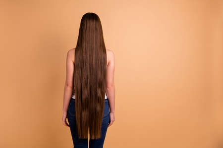 Photo pour Close up back rear behind view photo beautiful amazing her she lady very long brown hair showing great condition every curl wear casual white tank-top jeans denim isolated pastel beige background - image libre de droit