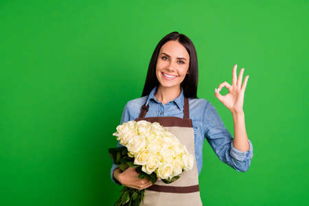 Photo for Portrait charming attractive lovely lady assistant salesperson entrepreneur ads advertisement choice decision promo product botany environment rosebud shirt blue denim jeans isolated green background - Royalty Free Image