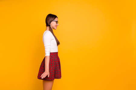 Foto de Profile side view portrait of nice-looking sweet attractive lovely cheerful cheery girl wearing uniform standing straight isolated over bright vivid shine yellow background - Imagen libre de derechos