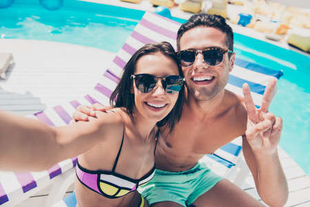 Photo pour Cute pair spending honeymoon enjoying sunny day taking selfies showing v-sign symbol - image libre de droit
