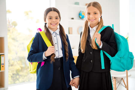 Photo pour Portrait of two person nice adorable attractive charming cute lovely cheerful cheery friendly girls new academic year 1 September holding hands in light white interior class room indoors - image libre de droit