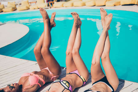 Photo pour Nice attractive sporty perfect girls lying on wooden floor enjoying life lifestyle fit thin slender crossed legs glamour resort spa tour recreation bachelorette weekend at roof top outdoors - image libre de droit