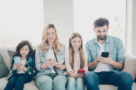 Photo pour Young family two adopted children cozy sitting sofa look telephones dont care each other addiction concept - image libre de droit