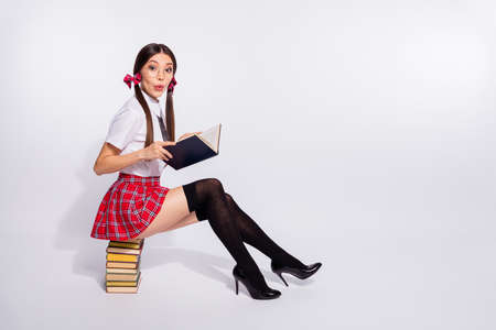Photo for Full length side profile body size photo beautiful she her teacher sit reader book pile interested curious story end finish tails wear short red checkered costume pantyhose isolated white background - Royalty Free Image