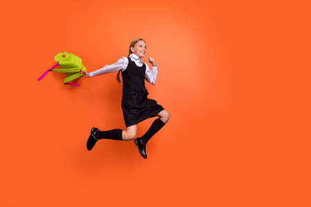 Full length body size view of her she nice attractive cheerful cheery pre-teen girl having fun after lesson active motion movement going home isolated on bright vivid shine orange background
