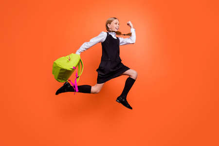 Full length body size view of nice attractive lovely cheerful cheery glad pre-teen girl having fun after lesson activity motion movement isolated on bright vivid shine orange background