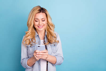 Photo pour Portrait of lovely cheerful lady looking into device smiling isolated over blue background - image libre de droit