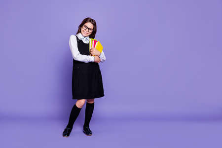 Foto de Full length body size view of nice attractive cheerful intelligent wavy-haired pre-teen girl ready to class holding in hands academic, literature isolated over bright vivid shine violet background - Imagen libre de derechos
