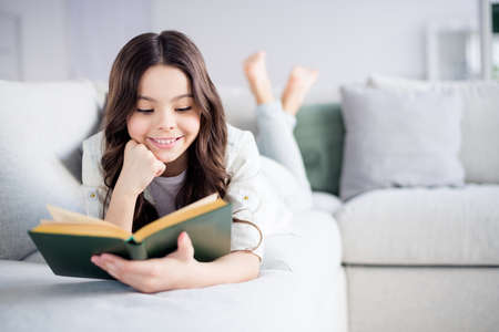 Foto de Portrait of her she nice attractive lovely charming cute cheerful cheery focused wavy-haired preteen girl lying on divan reading novel in light white interior living-room indoors - Imagen libre de derechos