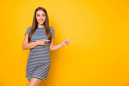 Foto de Photo of pretty lady indicating fingers empty space wear striped white blue dress isolated yellow background - Imagen libre de derechos