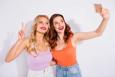 Photo pour Pretty ladies holding telephone hands making selfies showing v-sign wear casual tank-tops isolated white background - image libre de droit