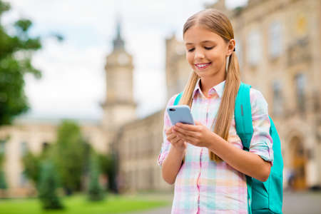 Photo pour Portrait of concentrated small girl using device holding rucksack backpack wearing checkered plaid t-shirt standing outside - image libre de droit