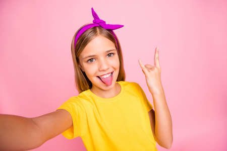 Photo pour Self-portrait of her she nice attractive lovely crazy cheerful cheery pre-teen girl wearing yellow t-shirt showing horn symbol heavy metal rock roll having fun isolated over pink pastel background - image libre de droit