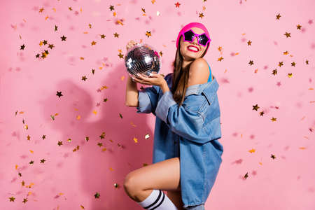 Foto de Portrait of elegant party youth holding mirror ball wearing denim jeans jacket eyewear eyeglasses isolated over pink background - Imagen libre de derechos