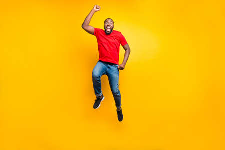 Photo pour Full length body size photo of jumping man wearing red t-shirt jeans denim rejoicing with his victory at something while isolated with yellow background - image libre de droit