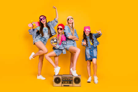 Photo pour Full length size photo of group of four people carefree students having fun discotheque white parents are absent. Wearing denim outfit showing horned signs isolated yellow background - image libre de droit