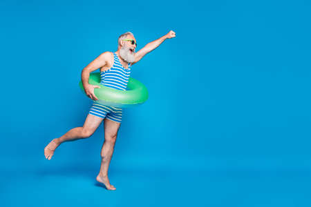 Foto de Full body profile side photo of retired pensioner raise his hand running holding green toy ring wear striped bathing suit eyewear eyeglasses isolated over blue background - Imagen libre de derechos