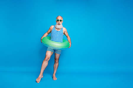 Photo pour Full size photo of impressed man in eyeglasses eyewear wearing striped bathing costume hold lifesaver trying ocean water isolated over blue background - image libre de droit