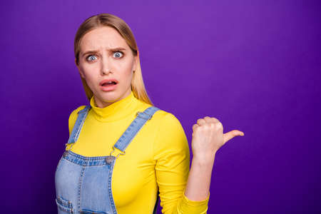 Photo for Portrait of impressed youth pointing at copy space wearing yellow turtleneck denim jeans overalls isolated over violet purple background - Royalty Free Image