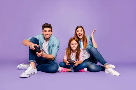 Foto de Photo of three family members sitting floor trying hard to win team game wear casual clothes isolated purple background - Imagen libre de derechos