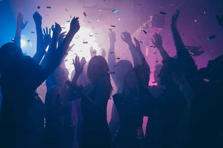Photo pour Close up photo of many party people dancing purple lights confetti flying everywhere nightclub event hands raised up wear shiny clothes - image libre de droit