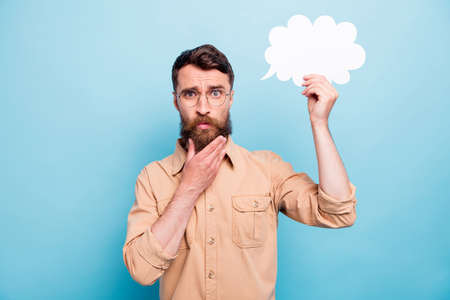 Foto de Portrait of minded man in eyewear eyeglasses holding paper card bubble touching his chin wearing brown shirt isolated over blue background - Imagen libre de derechos