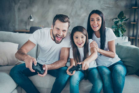 Photo pour Portrait of nice attractive lovely cheerful cheery funny family fan wearing casual white t-shirts jeans denim sitting on divan having fun video game spending free time indoors - image libre de droit
