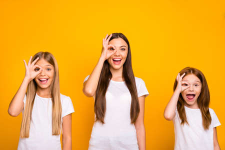 Foto de Funny three sister ladies holding hands in okey symbols near eye like specs wear casual outfit isolated yellow background - Imagen libre de derechos