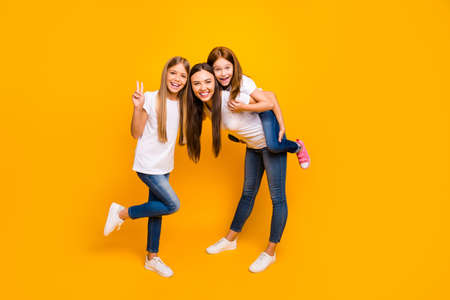 Photo pour Photo of funky three ladies showing v-sign spending leisure time wear casual clothes isolated yellow background - image libre de droit