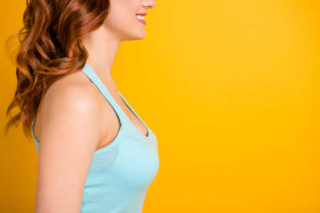 Foto de Cropped photo of cheerful nice girlfriend focused on her chest and boobs wearing turquoise tank-top while isolated over yellow vibrant color background - Imagen libre de derechos