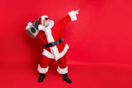 Photo pour Full length profile side photo of funny santa claus raise his arms dance wear stylish trendy eyewear eyeglasses hat headwear isolated over red background - image libre de droit