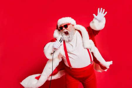 Foto de Closeup photo of funny funky wild vocalist screaming in microphone wearing fur coat gloves suspenders isolated bright background - Imagen libre de derechos
