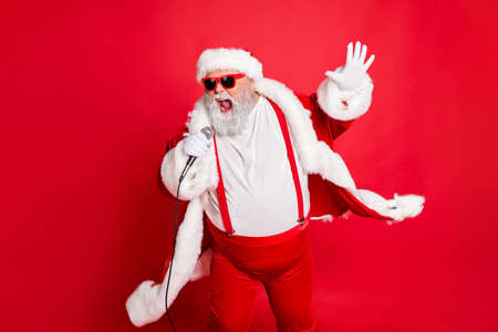 Photo pour Portrait of cool funny fat overweight santa claus with big belly sing song on christmas party wear style stylish trendy eyeglasses eyewear hat isolated over red background - image libre de droit