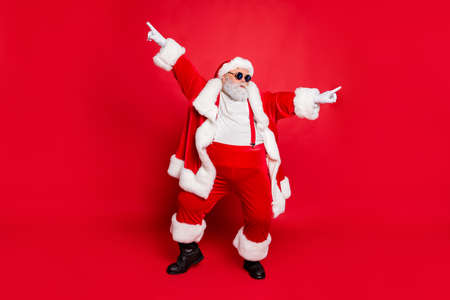 Foto de Full body photo of funky fat santa claus with big funny abdomen dancing raising arms wearing style stylish trendy eyewear eyeglasses isolated over red background - Imagen libre de derechos